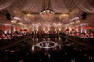 wedding-reception-ballroom-black-dance-floor-white-monogram-chandelier-red-rose-centerpieces