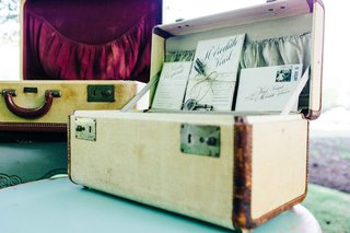 a-couples-wedding-invitation-suite-displayed-inside-vintage-luggage-at-the-couples-ceremony