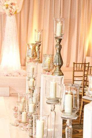 candles-in-metallic-stands-and-vessels-line-the-wedding-aisle