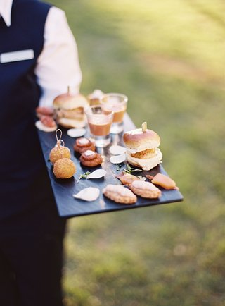 server-holding-platter-tray-with-balls-soup-shooters-slider-appetizers-outdoor-cocktail-hour