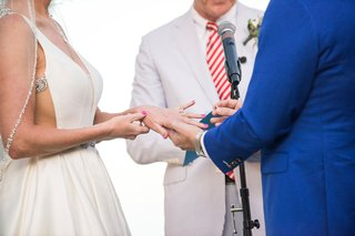 groom-places-ring-on-brides-finger-at-beach-wedding