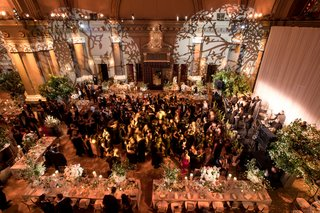 wedding-reception-light-projections-on-wall-tree-branch-designs-flowers-guests-on-dance-floor