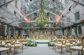 wedding-ceremony-open-tent-area-greenery-flower-chandelier-gold-oval-back-chairs-stage-greenery