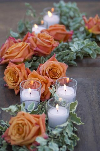 orange-roses-with-greenery-and-small-white-candles