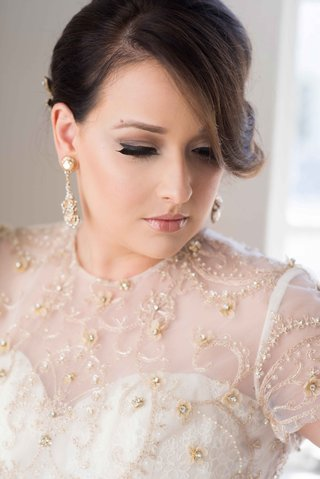 bride-with-beautiful-makeup-and-updo-with-diamond-earrings-and-ball-gown-with-gold-flower-details