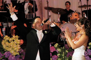 bride-claps-next-to-groom-with-microphone-at-wedding-reception