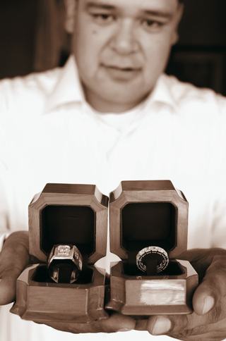 sepia-tone-image-of-groom-holding-wedding-ring-boxes