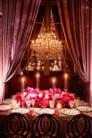 wedding-reception-table-chandelier-drapery-pink-red-rose-flowers-butterfly-china-plates-taper-candle