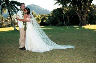 bride-and-groom-in-casual-island-outfit-in-filed-overlooking-mountain