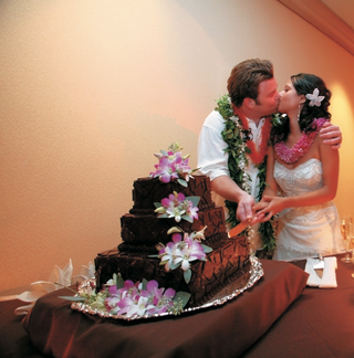 newlyweds-cut-chocolate-cake-with-pink-flowers