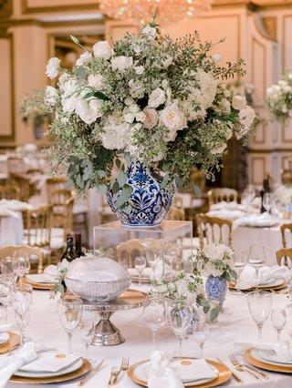 wedding-reception-centerpiece-white-flower-greenery-blue-white-vase-acrylic-riser-gold-details