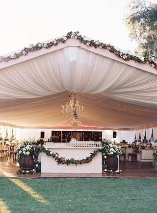 wedding-reception-bar-with-magnolia-leaf-garland-in-tent-draping-chandeliers-string-lights