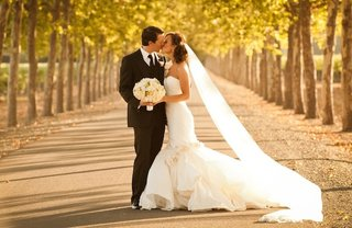 couple-kissing-on-roadway-between-trees