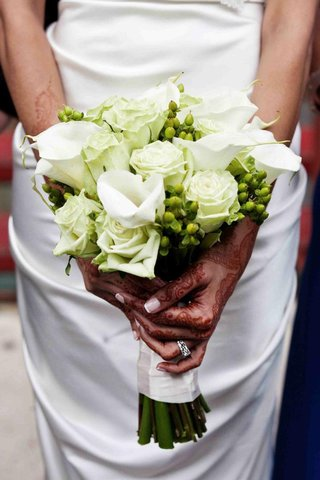 bride-with-henna-on-hands-holds-white-bouquet