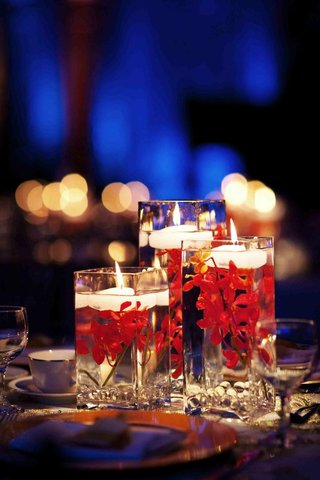 red-flowers-submerged-in-glass-vase-with-candle
