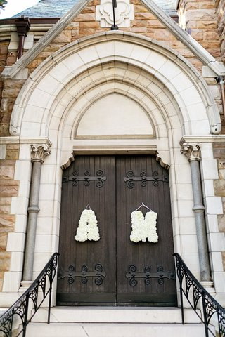 bride-and-grooms-initials-in-white-flowers-on-church-door
