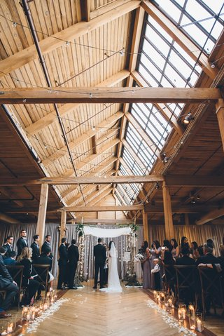 rustic-jewish-wedding-ceremony-beams-and-wood-floors-skylight-flower-petals-along-aisle