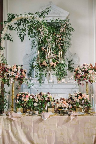 free-standing-chandelier-draped-with-greenery-at-the-center-of-table