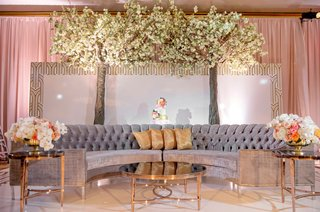 wedding-reception-flowered-trees-grey-tufted-semi-circle-sofa-gold-pillows-coral-pink-flowers-gold