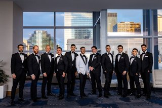 groom-in-white-tuxedo-jacket-black-bow-tie-groomsmen-in-black-and-white-suits-tuxes