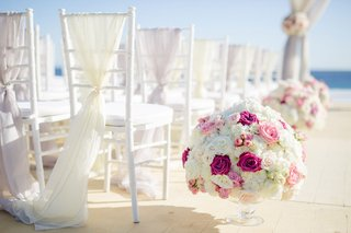 beach-wedding-ceremony-sheer-fabric-on-back-of-chair-small-flower-arrangements-round-rose-designs