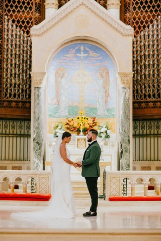 bride-and-groom-holding-hands-traditional-church-wedding-miami-altar-white-flowers-greenery