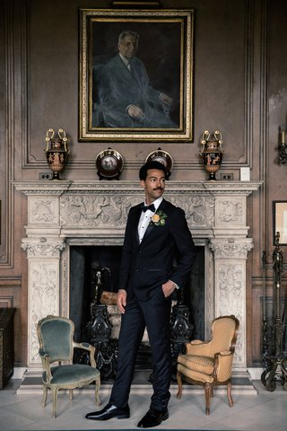 styled-wedding-shoot-groom-in-tuxedo-in-front-of-elegant-fireplace-with-portrait