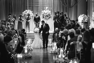 black-and-white-photo-of-couple-walking-up-aisle