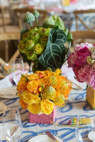 yellow-flowers-protea-roses-in-pink-eraser-vase-on-table-with-cursive-blue-and-white-linen