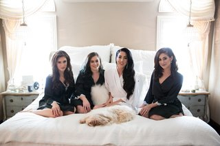 bride-in-white-robe-bridesmaids-in-black-robe-on-bed-with-dog