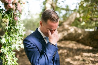 groom-in-navy-blue-suit-holding-back-tears-crying-at-outdoor-wedding-ceremony