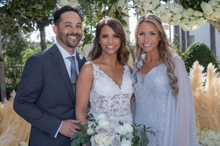 bride-in-embroidered-wedding-dress-with-sheer-details-with-family-members-in-grey-silver-tones