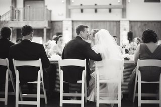 newlyweds-sitting-at-table-kiss