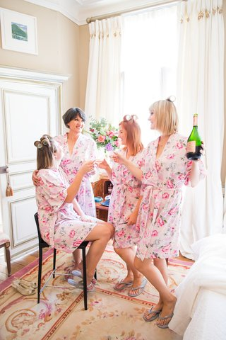 bridesmaids-and-bride-getting-ready-in-pink-white-flower-print-robes-drinking-champagne-hair-curlers