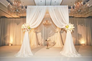 jewish-wedding-ceremony-in-chicago-with-white-drapes-flower-tie-backs-with-roses-chandeliers