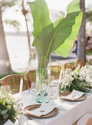 tropical-destination-wedding-centerpiece-palm-leaves-in-tall-vase-rattan-charger-plates-greenery
