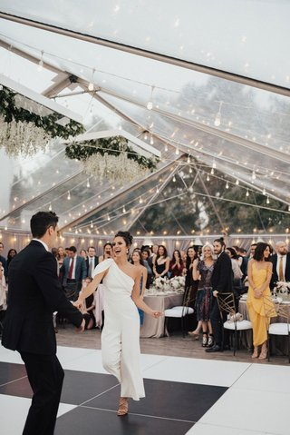 bride-changed-into-one-shoulder-white-jumpsuit-for-dance-clear-tent-string-lights-black-white-floor