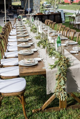 farm-wedding-reception-wood-table-with-tan-runner-leafy-garland-candles-on-grassy-space