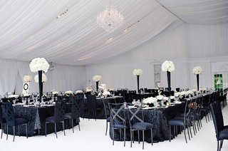 white-tent-with-flower-centerpieces-and-black-linens-and-chairs