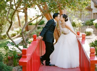 bride-and-groom-kiss-on-red-bridge