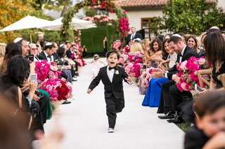cute-ring-bearer-in-tuxedo-bow-tie-and-sneakers-running-down-aisle-flower-girl-behind