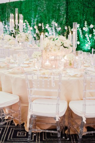 wedding-reception-with-clear-chiavari-chairs-blush-linens-ivory-centerpiece-with-tapered-candles