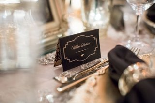 black-and-gold-place-card-with-menu-selection-icon-cow-on-escort-card-tent-format