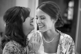 black-and-white-photo-of-bride-and-her-mother-laugh-before-getting-ready-for-wedding-ceremony