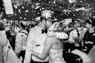 black-and-white-photo-of-bride-and-groom-in-new-years-eve-hat-and-tiara-wedding-kiss-confetti