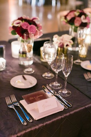 dark-wedding-colors-purple-linens-with-menu-in-napkin-and-low-centerpieces-pink-and-purple-blooms