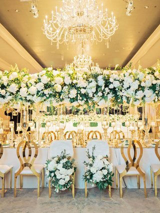 wedding-reception-head-table-fur-bride-groom-chairs-gold-seating-tall-centerpiece-overhead-crystals