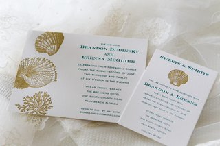 white-invitations-with-blue-print-and-gold-seashells