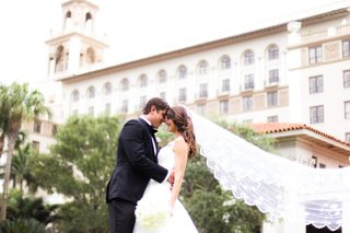 groom-and-bride-with-long-veil-in-front-of-breakers-resort