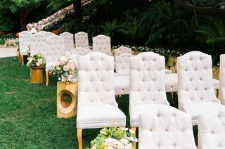 grey-tufted-chairs-for-ceremony-with-wood-side-tables-flowers-in-vase-green-lawn-grass